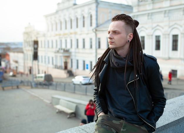 Rocker rock star young man walking on the city street autumn day Premium Photo