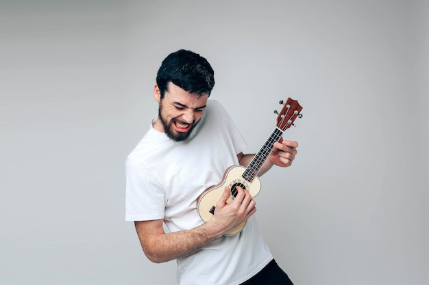 Rocking alone during playing on ukulele. musician practicing and having fun alone Premium Photo
