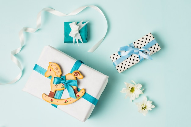 Rocking horse toy with gift boxes; flowers and ribbon over blue backdrop Free Photo