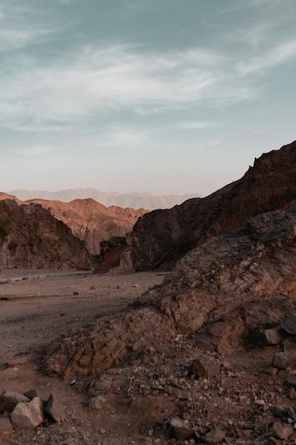 Rocce e colline in un deserto sotto il cielo nuvoloso Foto Gratuite