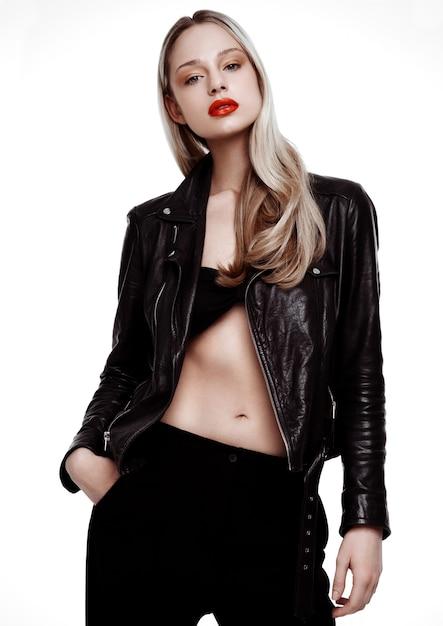 Rockstar байкерская модель девушка носить кожаную куртку. длинные светлые волосы и красные губы. студия выстрел на белом фоне Premium Фотографии