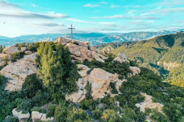 Scogliera rocciosa coperta di verde con una croce posta sulla cima e bellissime montagne Foto Gratuite