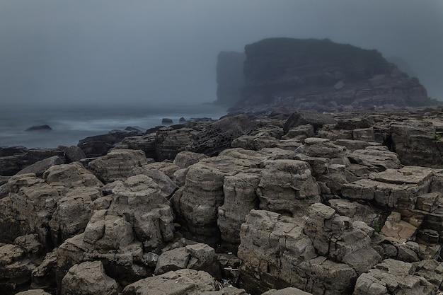 Rocky coastline and high cliffs hidden in mis Premium Photo