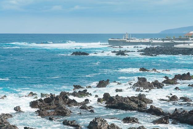 プエルトデラクルーズの岩の多い海岸。大西洋の波が晴れた日、テネリフェ島、スペインの岩の上を転がる 無料写真
