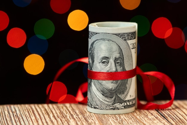 Roll of 100 us dollar bills with ribbon against of colorful lights Premium Photo
