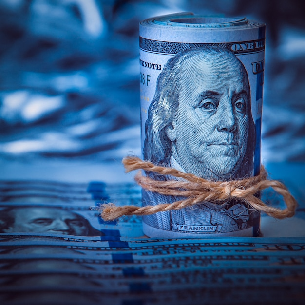 A roll of dollars on the background of scattered hundred dollar bills in blue light. Premium Photo
