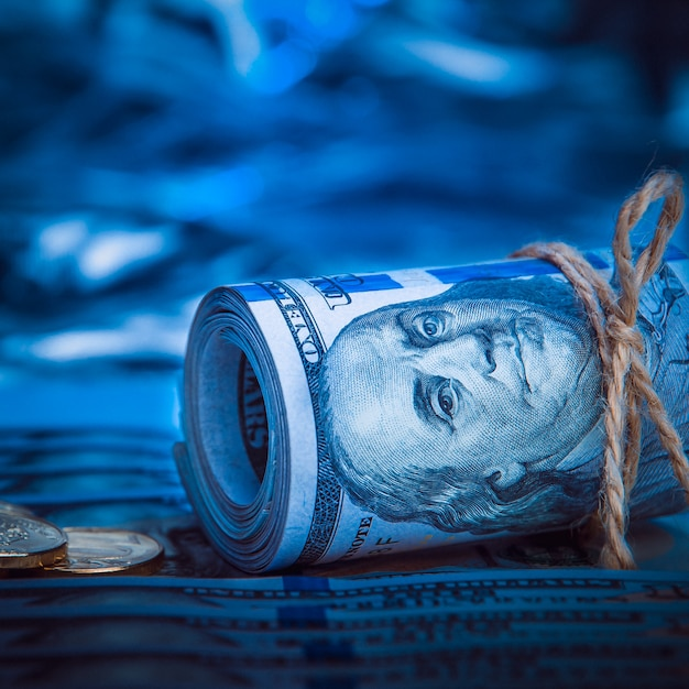A roll of dollars with coins on the background of scattered one hundred dollar bills in blue light. Premium Photo