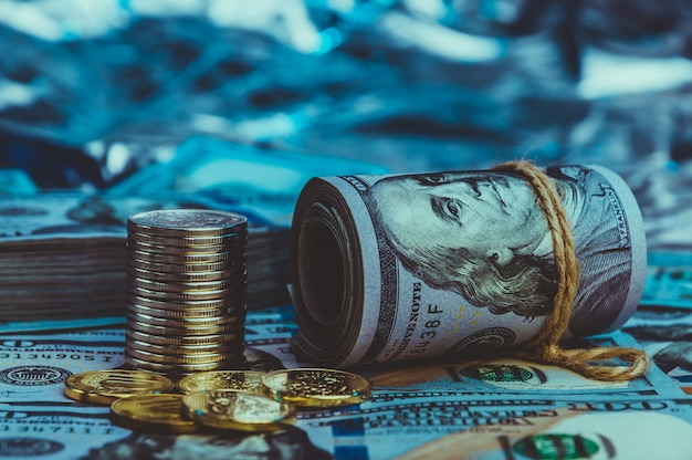 A roll of dollars with coins on the background of scattered