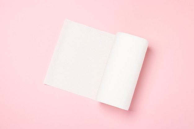 Roll of paper towels on a pink surface. concept is 100 natural product, delicate and soft. flat lay, top view. Premium Photo