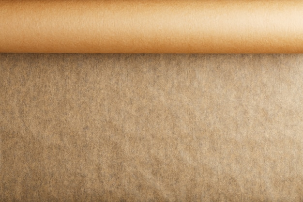 A roll of unfolded brown parchment paper, for baking food in on a dark background, top view. Premium Photo