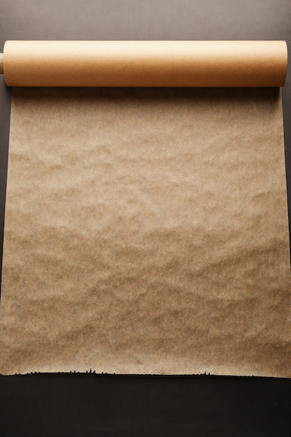 A roll of unfolded brown parchment paper for baking food in on dark Premium Photo