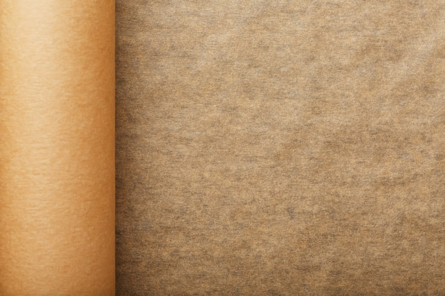 A roll of unfolded brown parchment paper, for baking food in on dark Premium Photo