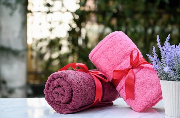 Roll up of colorful towels on white table with copy space on blurred garden background. Premium Photo