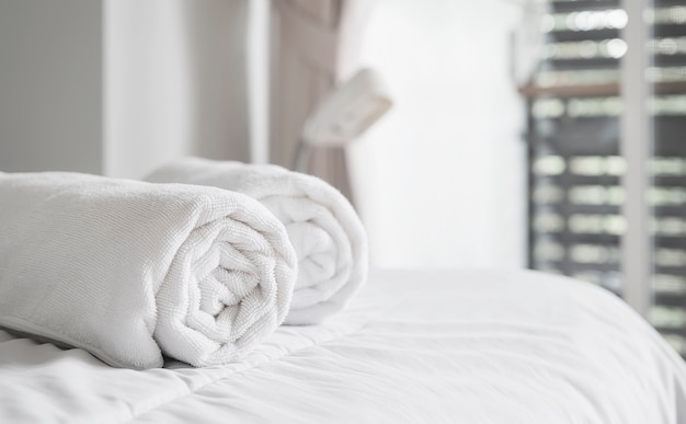Roll of white clean bath towels on the bed in hotel room. copy space. Premium Photo