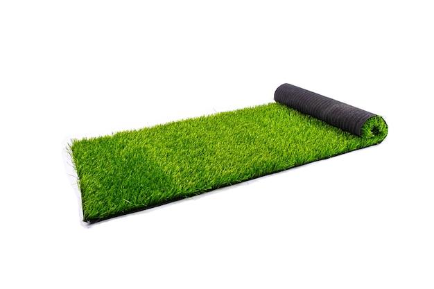 Рулон с искусственным зеленым газоном на белом фоне, покрытие для детских и спортивных площадок. Premium Фотографии