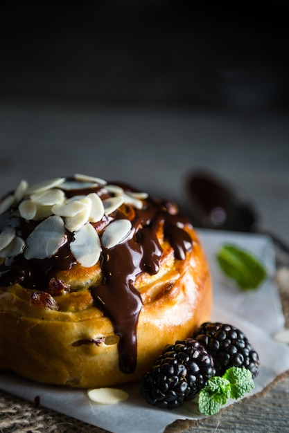 Roll with chocolate, nuts and berries, dark stone table Premium Photo