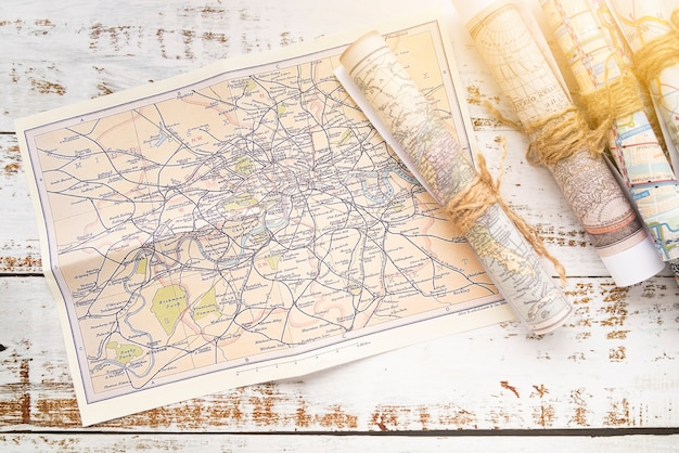 Rolled maps on a wooden desk Free Photo