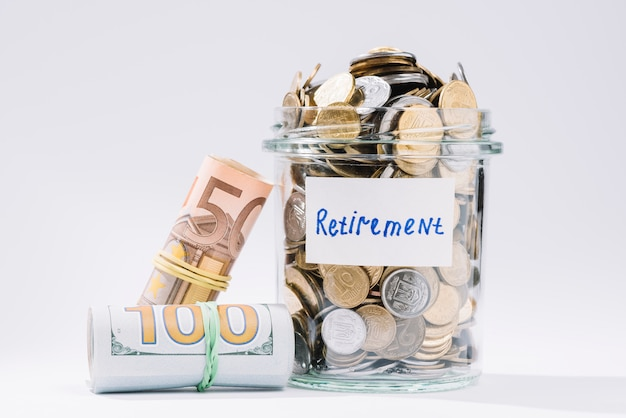 Rolled up banknotes and retirement container full of coins on white background Free Photo