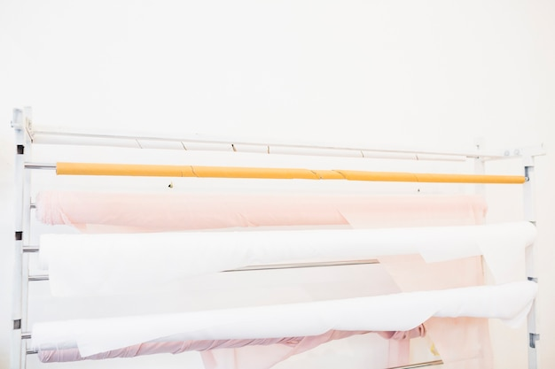 Rolled up pink and white fabrics in tailor shop Free Photo