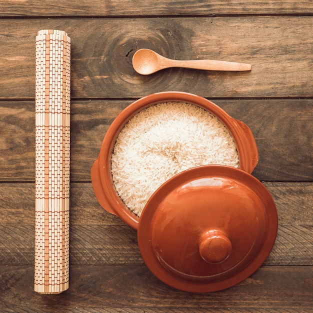Rolled up place mat with rice in brown pot with lid and wooden spoon Free Photo