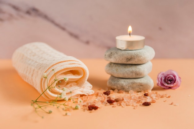 Rolled up towel; lighted candle over the spa stones; rose and himalayan salts on peach colored backdrop Free Photo