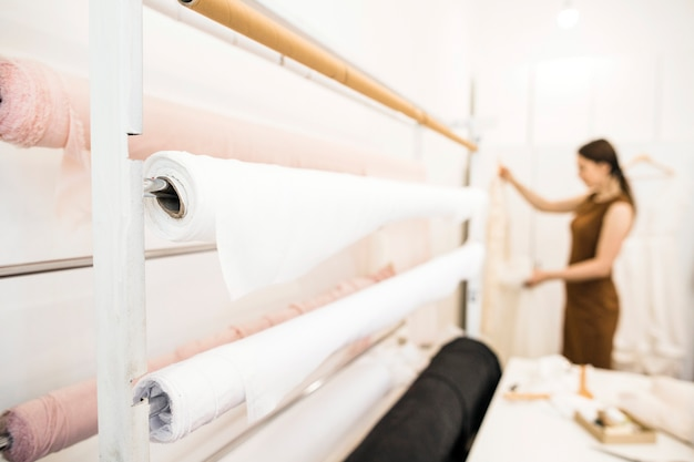 Rolled up white fabrics in tailor shop Free Photo