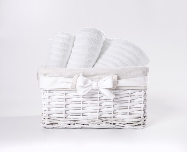 Rolled white soft terry towels in the basket against a white backdrop. striped towels in a white basket in front of a white backdrop. Premium Photo