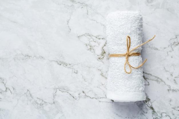 Asciugamano bianco arrotolato per il trattamento termale messo sul pavimento in marmo bianco Foto Gratuite