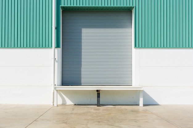 Roller shutter door and dock leveler ramp outside factory building Premium Photo