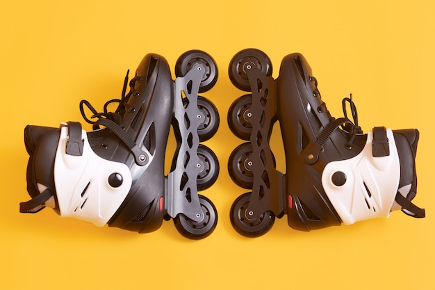 黄色に分離されたローラースケート、新しいクールな白と黒のローリングスケートのペア、アクティブなスポーツトレーニング用の機器、リンク、ローラースケート、ローラーブレード。アクティブな休息のコンセプトです。 無料写真