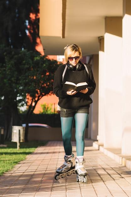 Roller skating woman enjoying book Free Photo