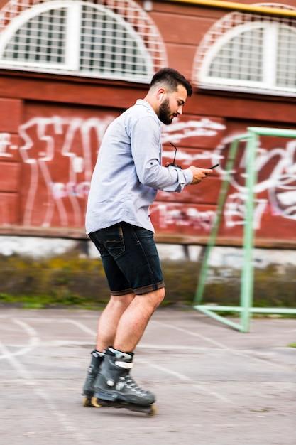 スケートパークでのrollerkating中に携帯電話を使用している男の側面図 無料写真