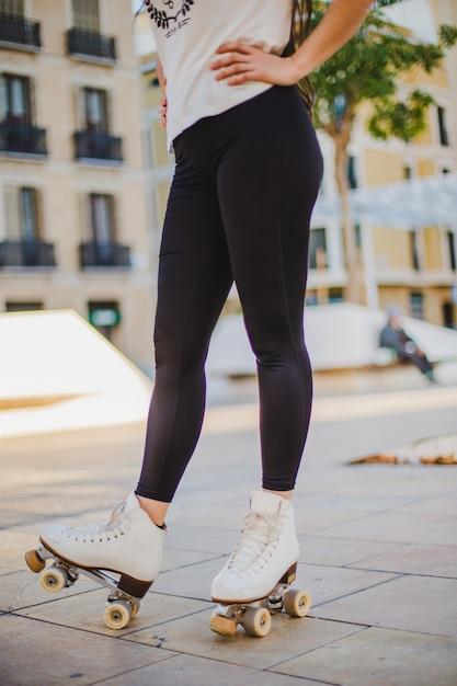 Женщина, носить rollerskates, стоя на тротуаре Бесплатные Фотографии