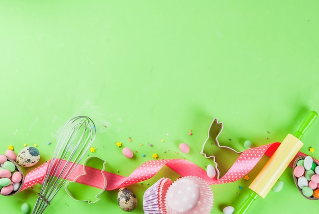 Rolling pin, whisk for whipping, cookie cutters, sugar sprinkling and flour on light green background Premium Photo