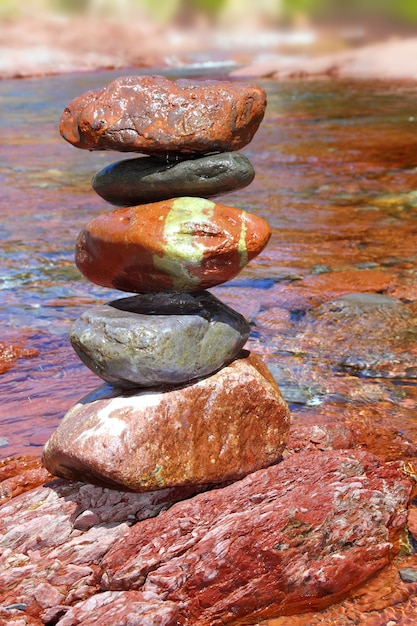 Rolling stones stacked red rodeno limestone in river Premium Photo