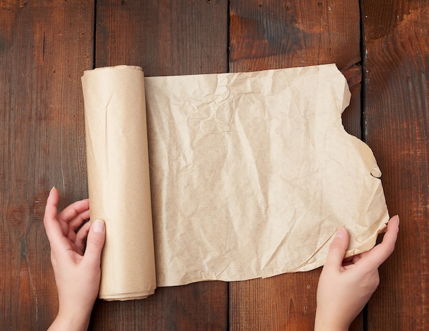 Rolls of brown parchment paper on a wooden surface Premium Photo