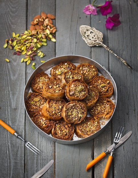 Rolls made with pumpkin seeds and almonds in a metal pot on a wooden surface Free Photo