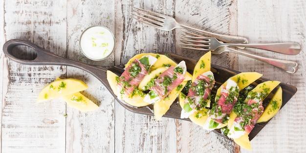 Rolls of mozzarella, basil and parma ham Premium Photo