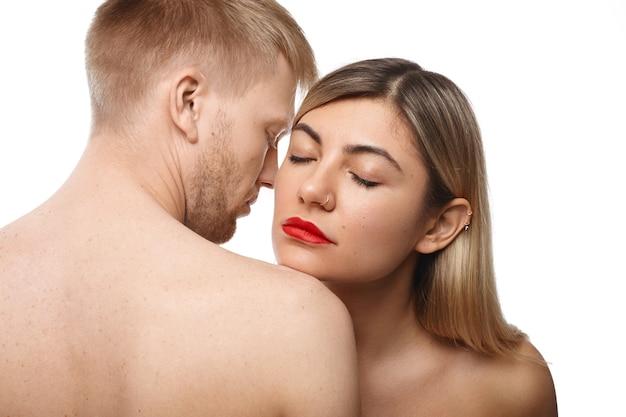 Concetto di romanticismo e passione. immagine di attraente coppia caucasica adulta che stringe a sé: bella donna con rossetto rosso e anello al naso chiudendo gli occhi, inalando il buon odore di corpo del suo uomo barbuto Foto Gratuite
