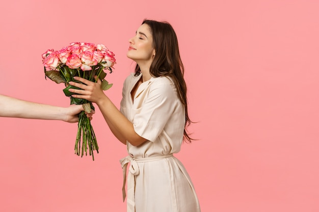 Romance, valentines day and happiness concept. gorgeous young woman receiving delivery, smelling pretty roses as hand extending bouquet to girl, smiling delighted, got surprise gift Premium Photo
