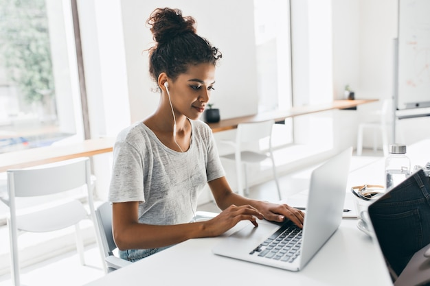 Romantic african woman with trendy hairstyle sitting at her workplace and analysing data. indoor portrait of black female student working with laptop before exam. Free Photo