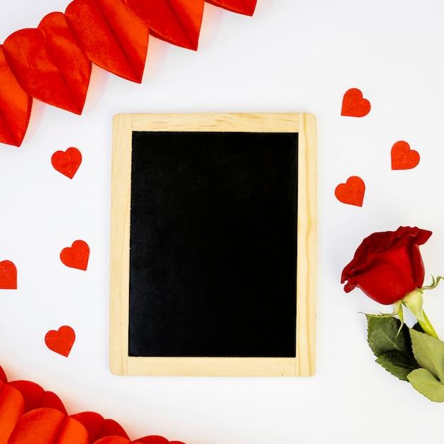 Romantic arrangement of blackboard and rose Free Photo