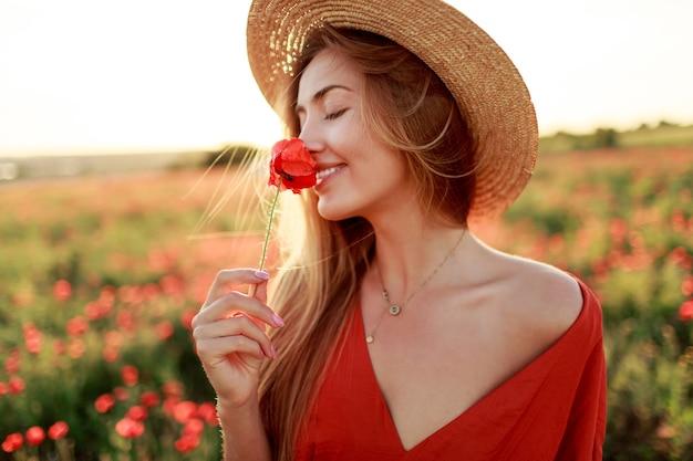 素晴らしいケシ畑を歩いて手に花とロマンチックなブロンドの女性。暖かい夕日の色。麦わら帽子。赤いドレス。柔らかな色。 無料写真