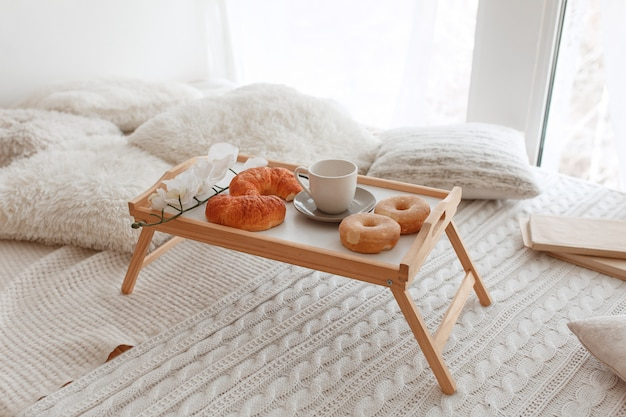 Romantic breakfast in bed on a wooden tray with croissants, donuts and orchid flowers Free Photo