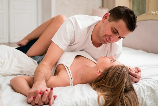 Romantic couple in bed smiling | Free Photo