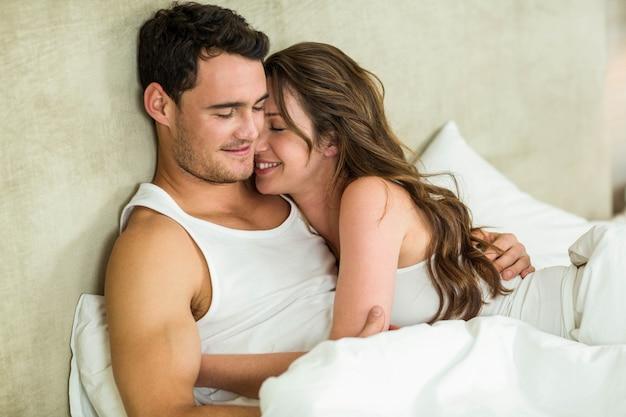 Premium Photo | Romantic couple cuddling on bed in bedroom
