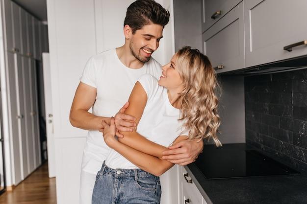 Романтическая пара танцует вместе с искренней улыбкой. крытый портрет счастливой семьи, позирующей на кухне. Бесплатные Фотографии