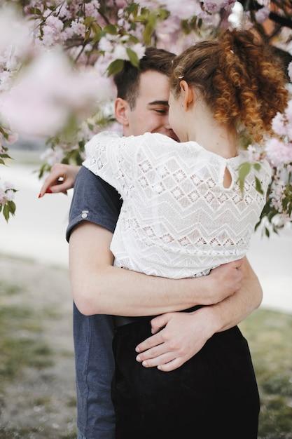 花の春の木の下でロマンチックなカップルを抱擁します。 無料写真