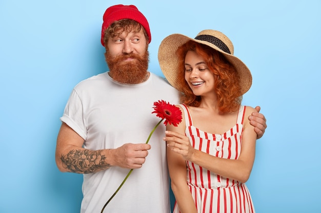 Романтичная влюбленная пара испытывает любовь друг к другу, бородатый рыжий парень с любовью обнимает девушку Бесплатные Фотографии