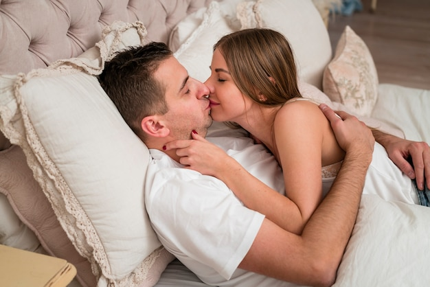 Romantic couple kissing in bed Free Photo